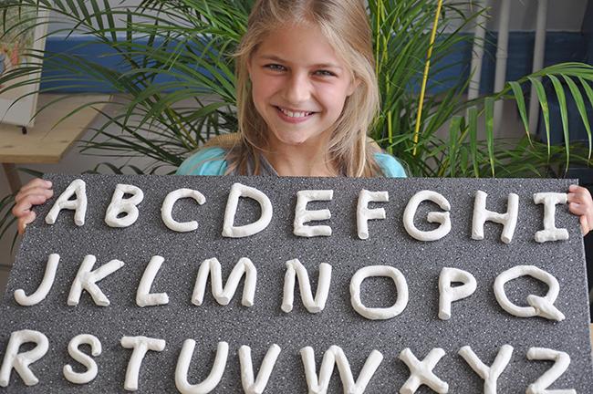 meisje bij instituut O,zo met letters van klei